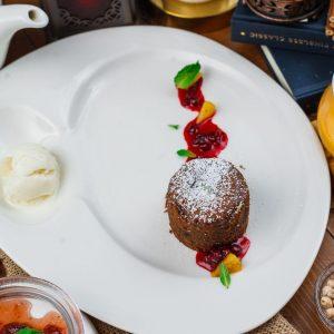 Шоколадный фондан с клюквой и апельсином подается с шариком мороженого